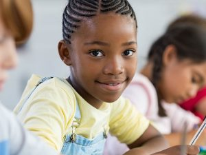 Smiling African American school girl in the class